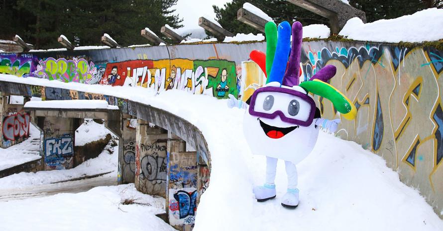 Das Maskottchen von EYOF 2019 Groodvy auf der verlassenen Bobbahn der Olympischen Spiele 1984. Foto: picture-alliance