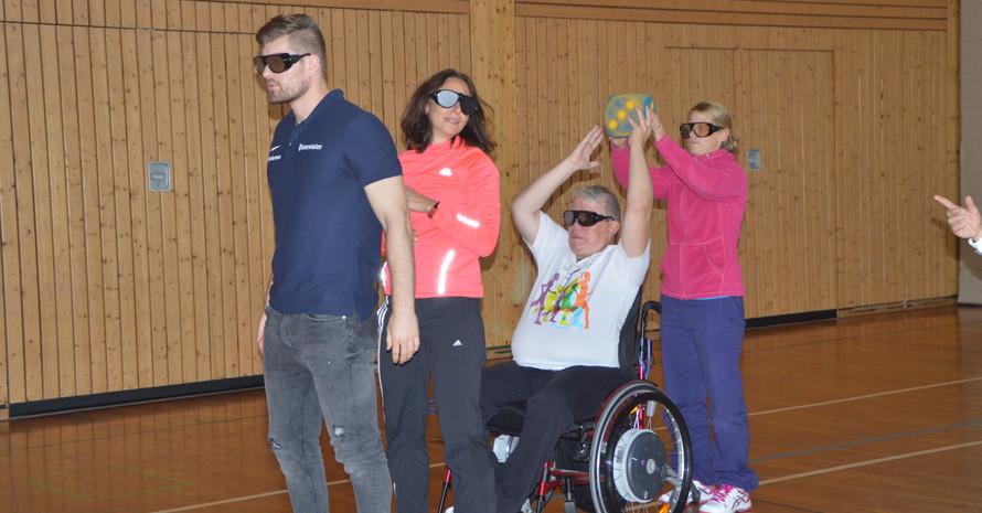 Vier Personen stehen hintereinander, darunter eine Person im Rollstuhl. Die Person, die hinten steht übergibt einen Schaumstoffwürfel der Person die vor ihr steht. Alle tragen Simulationsbrillen.