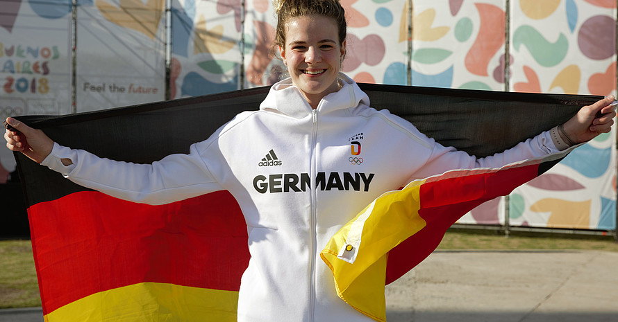 Elena Wassen mit deutscher Fahne im Olympischen Jugenddorf in Buenos Aires. Quelle: DOSB