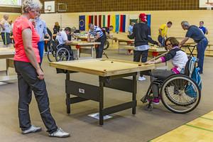 Zwei Frauen spielen an einem quadratischen Holztisch, ähnlich Billiard. Eine der Frauen sitzt im Rollstuhl.