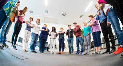 11 Teilnehmende stehen im Kreis und halten sich mit überkreuzten Armen an den Händen