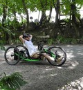 Thorsten Ely sitzt entspannt auf dem Handbike an einem Straßenrand. Er hat beide Arme hinter dem Kopf verschränkt.