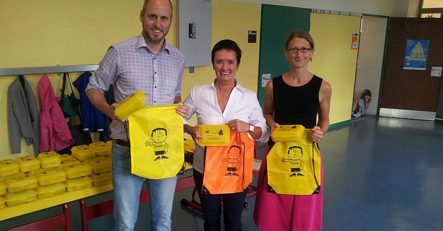 Umweltdezernentin Rosemarie Heilig (m.) verteilt Brotboxen und Trimmy-Turnbeutel mit Lehrern der  Bonifatiusschule. Foto: UFO RM
