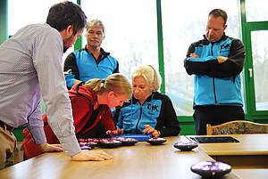 Fünf Männer und Frauen stehen an einem Tisch auf dem blinkende Scheiben und ein Tablet liegen. Eine Frau bedient und erklärt das Tablet.