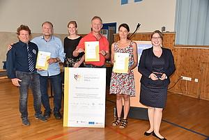 Artemis Toebs vom Deutschen Engagementpreis (1. von rechts) und Laura Pschorn vom Deutschen Olympischen Sportbund überreichen die Nominierungsurkunde an den sportlichen Leiter des TV 1848 Erlangen, Günther Beierlorzer (3. von rechts).
