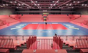 Eine leere Sporthalle mit rotem Boden und leeren Rängen