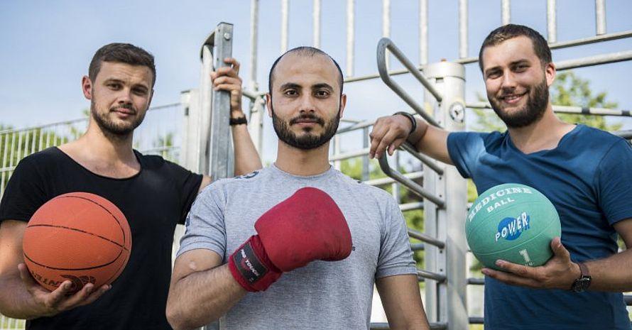 Am Eingang des Sportplatzes Hohenloh: Thomas Frank vom Kommunalen Integrationszentrum (links) und Christopher Tegethoff vom KSB (rechts) heißen Hazem Shihab willkommen.
