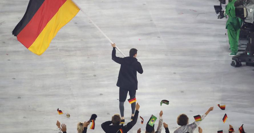 Tischtennisspieler Timo Boll schwenkt ind er Bildmitte die deutsche Fahne. Man sieht ihn von hinten. Ihm folgen weitere Athleten, die kleine deutsche und brasilianische Fahnen schwenken