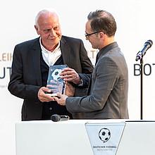 Otto Pfister (l.) erhält den Ehrenpreis von Außenminister Heiko Maas. Foto: Deutscher Fußball Botschafter