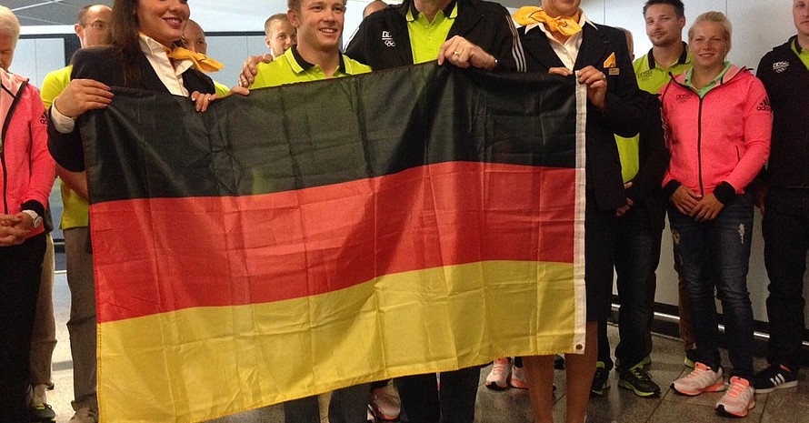 Flankiert von zwei Stewardessen der Lufthansa nimmt Fabian Hambüchen die deutsche Flagge vom DOSB-Vorstandsvorsitzenden Michael Vesper entgegen. Foto: DOSB