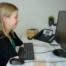 Eine Frau sitzt an einem Schreibtisch und arbeitet an einem Computer. Sie hat verkürzte Oberarme.