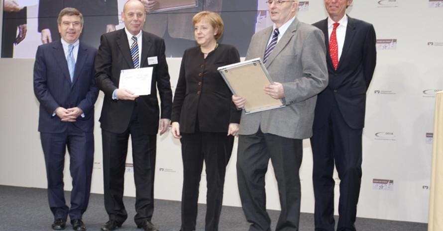 DOSB-Präsident Dr. Thomas Bach, Theodor Winkelmann von der Volksbank Koblenz, Bundeskanzlerin Angela Merkel, Vereinsvertreter Manfred Kailing und der Präsident der Bundesverbandes VR Dr. Christoph Pleister (v.l) bei der Siegerehrung.