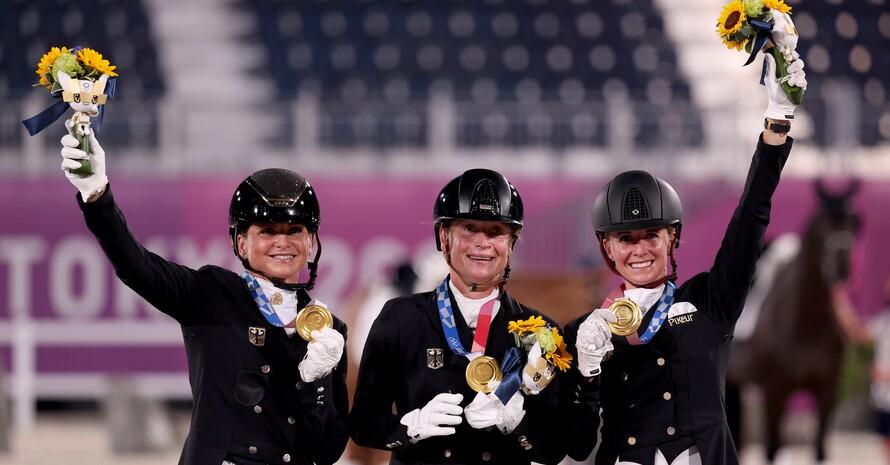 Dorothee Schneider, Isabell Werth und Jessica von Bredow-Werndl (v.li.) jubeln über die Goldmedaille im Dressur-Mannschaftswettbewerb. Foto: picture-alliance