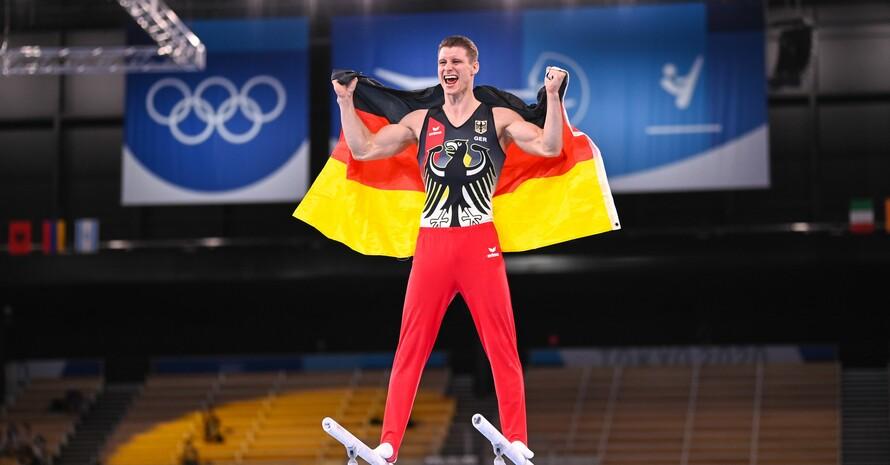Lukas Dauser steht auf den Holmen seines Paradegerätes und feiert seine Silbermedaille. Foto: picture-alliance