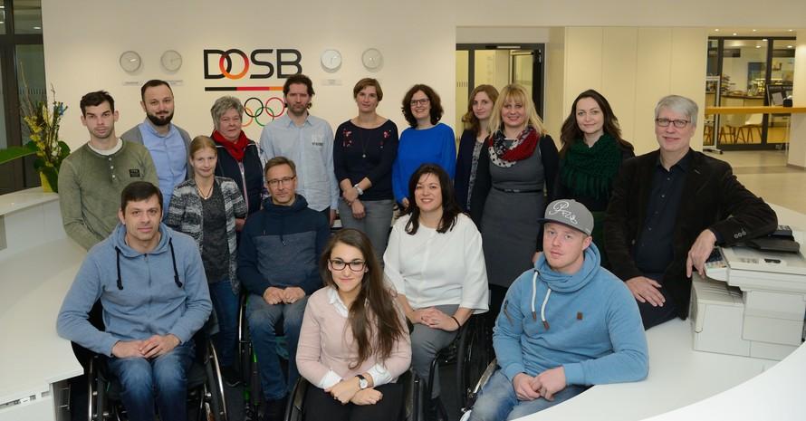 Gruppenfoto mit Sport-Inklusionsmanager/innen und dem Projekt-Team des DOSB. Männer und Frauen stehen gemeinsam im Kreis. Fünf davon nutzen einen Rollstuhl.