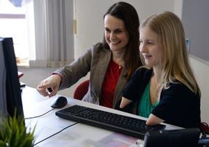 Zwei Frauen sitzen am Schreibtisch und schauen lächelnd auf den Bildschirm. Eine der beiden hat keine Unterarme und bedient die Tastatur.