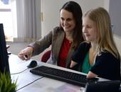Zwei Frauen sitzen am Schreibtisch und schauen lächelnd auf den Bildschirm. Eine der beiden hat keine Unterarme und bedient die Tatatur.