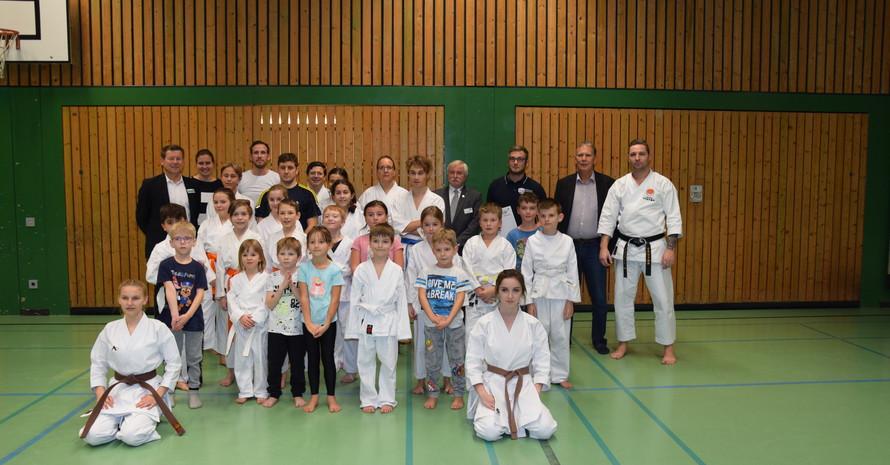 Ein Gruppenfoto mit Erwachsenen im Hintergrund und Kindern im Vordergrund in einer Sporthalle. Alle tragen normale Sportkleidung oder Karatekleidung.
