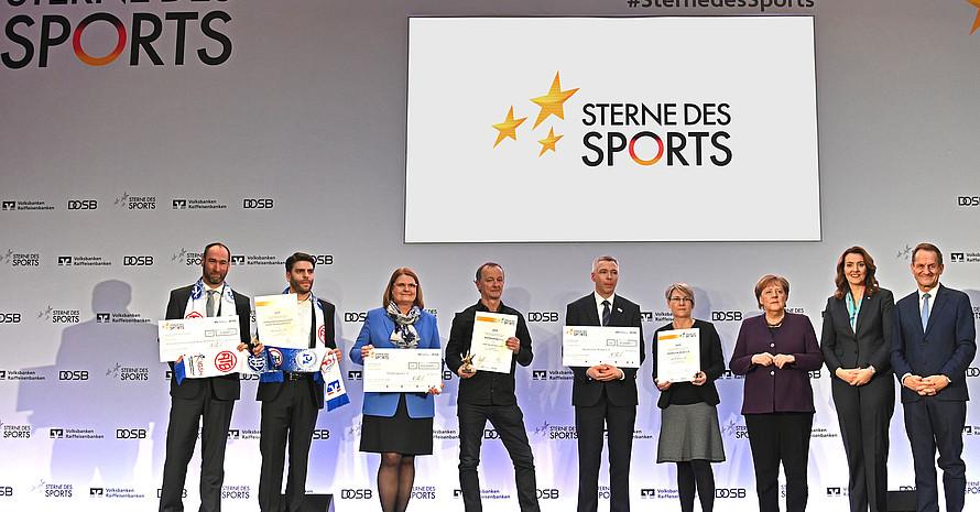 Die drei Siegervereine (v.li.) IG Heddesheim, Pfeffersport und SC Riesa)präsentieren stolz ihre Urkunden, die sie zuvor von Angela Merkel, Alfons Hörmann und Marija Kolak überreicht bekamen. Foto: BVR/DOSB/picture-alliance