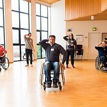 Es sind sechs Personen zu sehen, die tanzen. Davon sitzen drei im Rollstuhl.