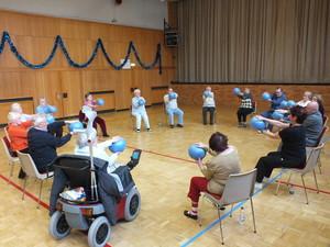 Eine Gruppe älterer Menschen trainiert im Stuhlkreis hält mit ausgestreckten Armen je einen blauen Balle Arme mit