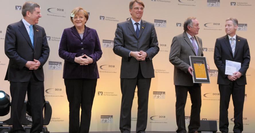 DOSB-Präsident Thomas Bach, Bundeskanzlerin Angela Merkel, BVR-Präsident Uwe Fröhlich mit Norbert Naperkowski vom Kneipp-Verein Bad Berka und Manfred Roth von der VR Bank Weimar (v.l.) bei der Preisverleihung in Berlin. Foto: Sterne des Sports