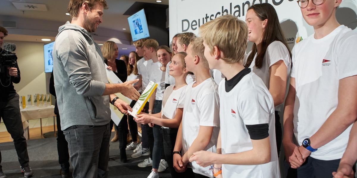 Botschafter Moritz Fürste überreicht den Pokal an den Mühlenberger Segel-Club. Foto: Markus Goetzke/DOSB