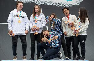 Evan Brandes und Lara Lessmann (v.l.) bei der Siegerehrung. Zusammen mit Argentinien gewannen die beiden Gold. Foto: OIS