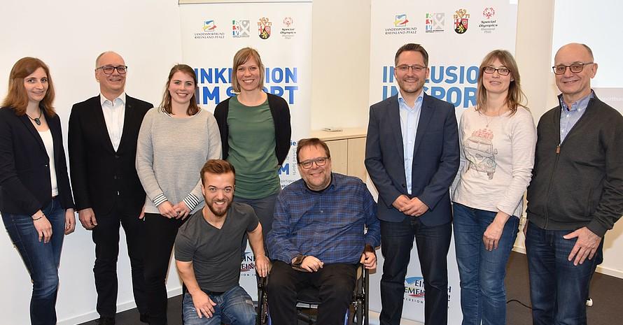 """Eine Gruppe von Menschen steht vor zwei Roll-Ups. Eine Person ist kleinwüchsig und eine Person sitzt im Rollstuhl. Auf den Roll-Ups sind Logos zu sehen und der Schriftzug """"Inklusion im Sport""""."""