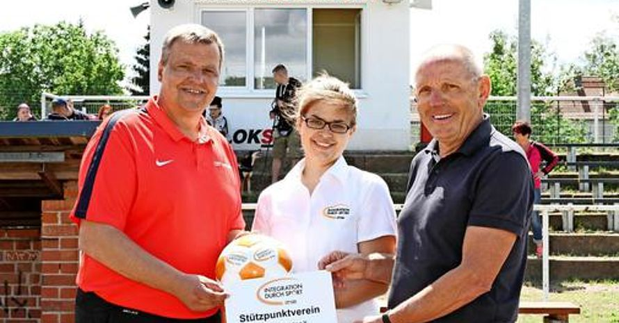 Vereinsvorstand Kurt Moryson (l.) und Vorstandsmitglied Bodo Schade (r.) nehmen von Sieglinde Czeglédi vom Kreissportbund Potsdam-Mittelmark das offizielle Schild und einen Fußball entgegen.