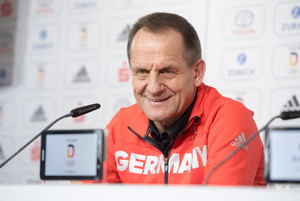 Alfons Hörmann in einem roten Pullover auf einer Pressekonferenz. Vor ihm ein Mikrofon. Er lacht.