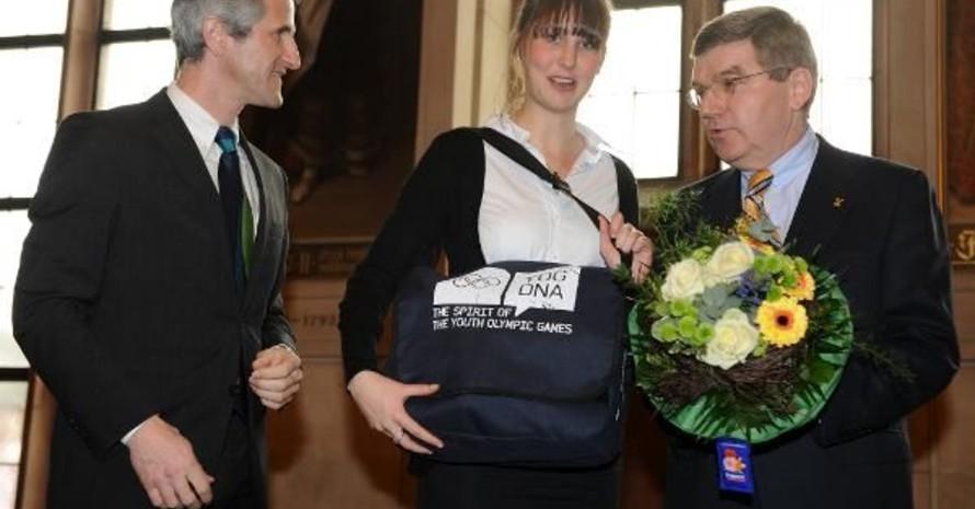 Thomas Bach und DOSB-Leistungssportdirektor Ulf Tippelt überreichten Karolin Weber ein Paket mit der Botschafter-Ausstattung für die Olympischen Jugendspiele im Sommer in Singapur. Copyright: picture-alliance