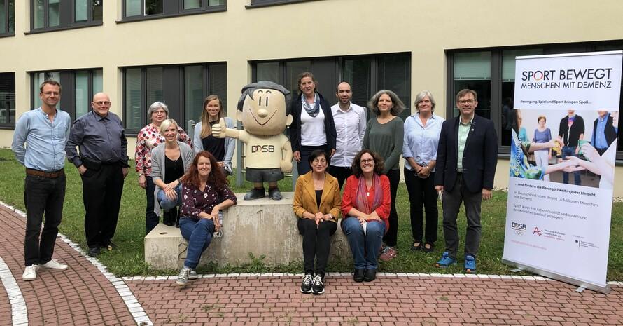 """Die Teilnehmenden der Projektgruppe """"Sport bewegt Menschen mit Demenz"""" stellen sich zum Gruppenbild mit dem DOSB-Trimmy. Foto: DOSB"""