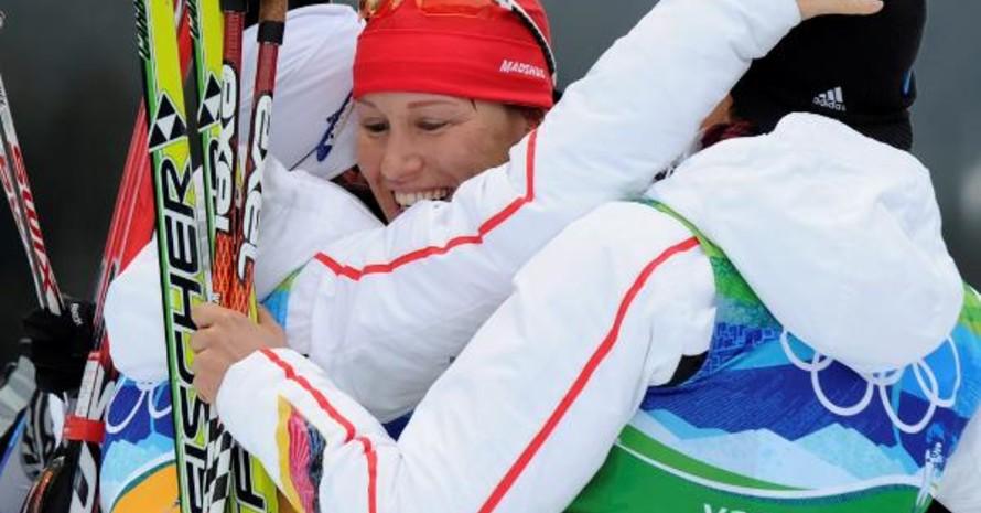 Startläuferin Kati Wilhelm lugt aus dem Knäuel des sich umarmenden Biathlon-Quartetts hervor. Copyright: picture-alliance