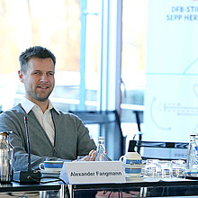 Alexander Fangmann sitzt an einem langen Konferenztisch in der Herberger-Stiftung