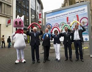 """Walter Schneeloch und Ute Schäfer präsentierten in der Kölner Innenstadt das neue Plakatmotiv der Kampagne """"Überwinde deinen inneren Schweinehund"""". Foto: Bilddatenbank LSB NRW"""