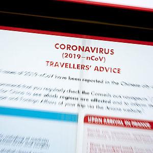 Hinweistafel zum Coronavirus am Flughafen für Reisende