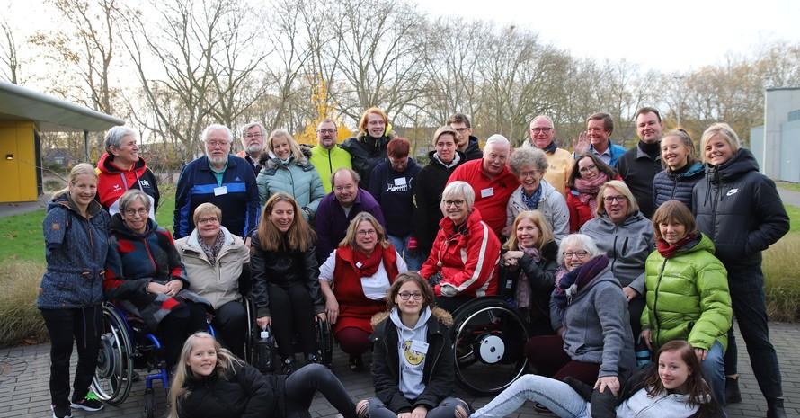 Gruppenfoto mit ca. 30 nichtbehinderten und behinderten Menschen, stehend, sitzend, zwei Liegen vor der Gruppe.
