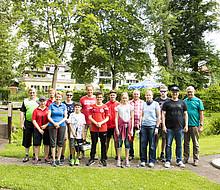Ein Gruppenfoto auf einer Minigolf-Anlage mit ca. 12 Teilnehmer/innen unterschiedlichen Alters und Geschlechts. Einige von ihnen halten einen Golfschläger in der Hand.