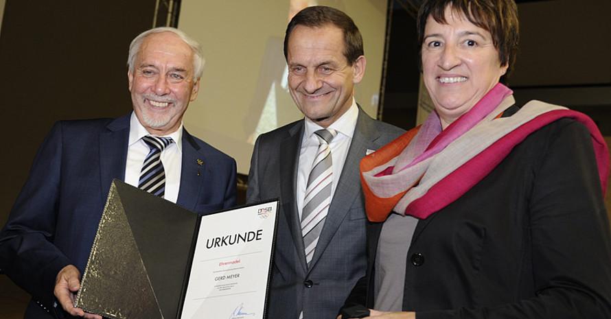 Gerd Meyer (l.) erhält die DOSB-Ehrennadel von DOSB-Präsident Alfons Hörmann und Karin Fehres, DOSB-Direktorin Sportentwicklung. Foto: LSVS/Becker&Bredel