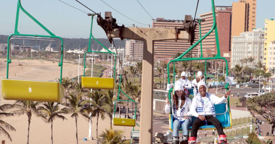 Winterspiele am Meer: Junge Südafrikaner machen im Sessellift in Durban Werbung für München 2018. Foto: München 2018