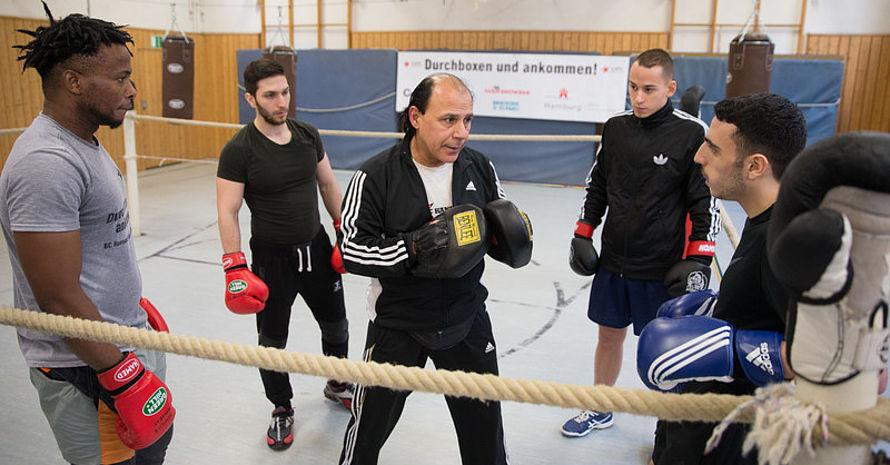 Hussein Ismail, Vereinsvorsitzender und Cheftrainer des BC Hanseat, trainiert im Boxclub Hanseat im Stadtteil St. Pauli in Hamburg mit den jungen Boxern (v.li.) Abiola (32) aus Nigeria, Saaer (25) aus Syrien, Finn (20) aus Hamburg, und Mudar (18), aus Syrien. Foto: picture-alliance