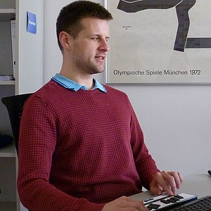 Alexander Fangmann sitzt an seinem Arbeitsplatz.