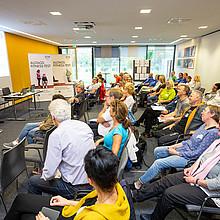 Blick in einen Raum. Viele Menschen sitzen in Stuhlreihen und betrachten einen Vortrag einer Dame vor einer Powerpoint-Präsentation.