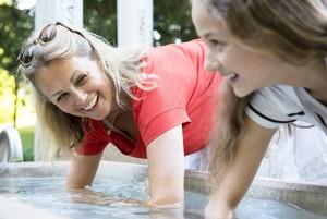 Zwei Frauen halten ihre Arme in ein Wasserbecken und schauen sich dabei gegenseitig lächelnd an.