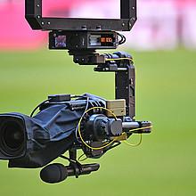 Eine Fernsehkamera (sogenannte Spidercam) hängt  über einem Sportfeld. Foto: picture-alliance
