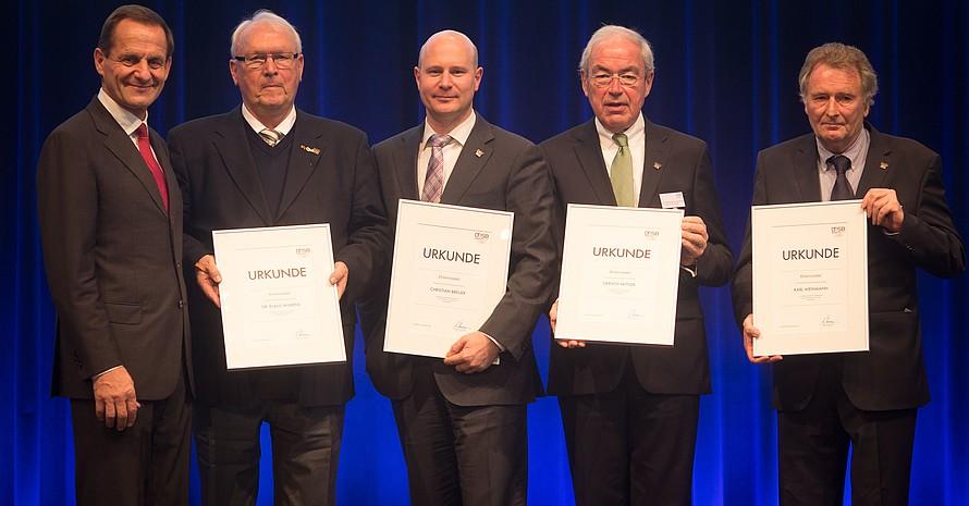 DOSB-Präsident Alfons Hörmann gratuliert den mit der DOSB-Ehrennadel ausgezeichneten (v.li.) Klaus Wilkens, Christian Breuer, Gernot Mittler und Karl Weinmann. Foto: Ronald Bonss