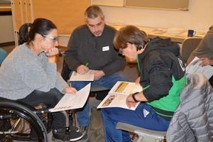 Drei Menschen sitzen zusammen und bearbeiten eine Aufgabe. Eine Person sitzt im Rollstuhl.
