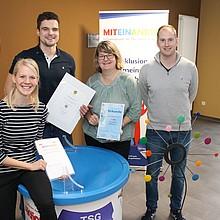 Das Bild zeigt die im TSG Hatten-Sandkrug am Thema Inklusion maßgeblich beteiligten fünf Personen mit Urkunden und dem Handbuch in den Händen. Im Hintergrund ist ein Roll-Up des Inklusionsprojekts zu sehen.