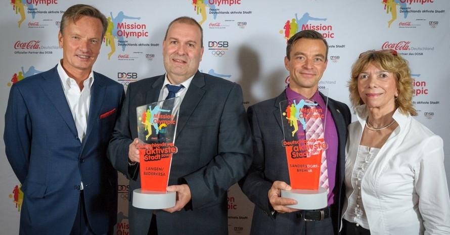 Prof. Dr. Gudrun Doll-Tepper vom DOSB (r.) und Hendrik Steckhan von Coca-Cola Deutschland (l.) gratulieren den Repräsentanten der Siegerstädte. Foto: Mission Olympic/André Wagenzik